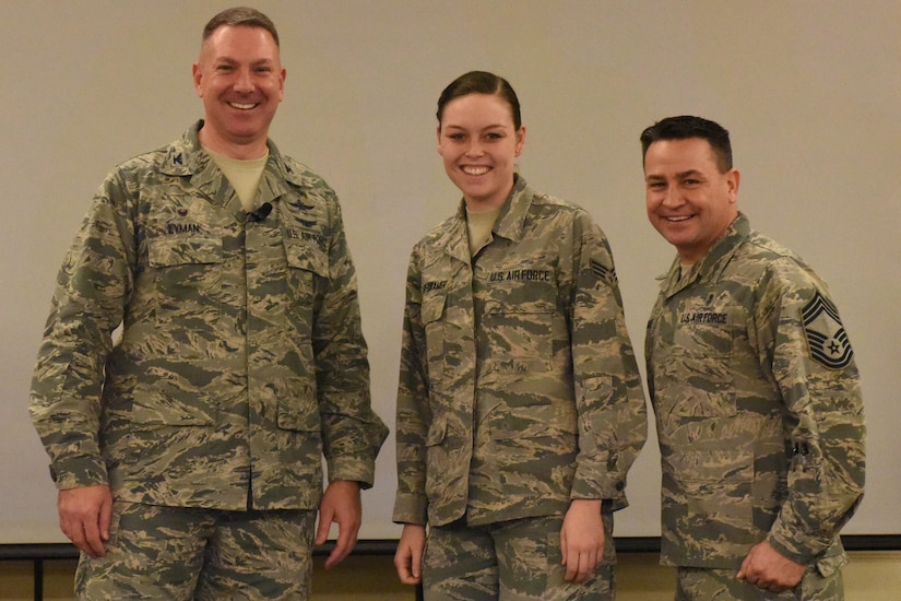 Senior Airman Allyson Walker-Cramer, center, 628th Civil Engineer Squadron engineer apprentice, is recognized by Col. Robert Lyman, left, 628th Air Base Wing commander, and Chief Master Sgt. Chad Ballance, right, 628th Medical Group superintendent, during a commander's call at the Charleston Club Feb. 3, 2017. Walker-Cramer was awarded the coin for coaching youth athletics. (U.S. Air Force photo by Airman Joshua R. Maund)