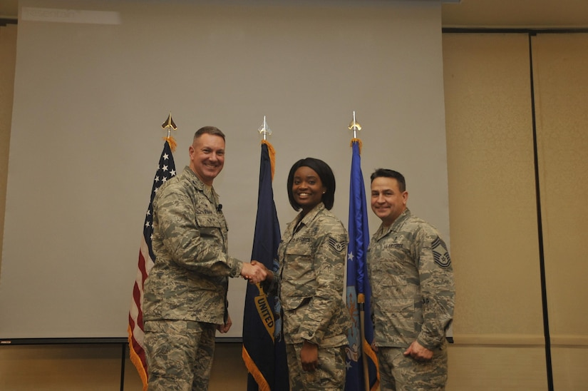 Staff Sgt. Amber Shepard, center, 628th Medical Group systems administrator, is recognized by Col. Robert Lyman, left, 628th Air Base Wing commander, and Chief Master Sgt. Chad Ballance, right, 628th Medical Group superintendent during a commander's call at the Charleston Club Feb. 3, 2017. Sheppard was recognized for improving the production and security of her unit and her involvement with the local community.