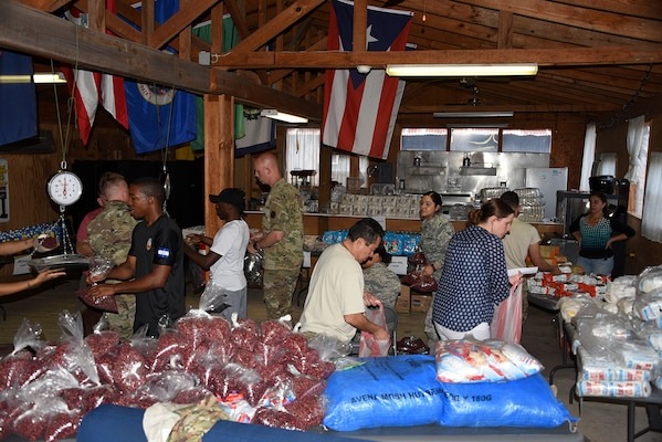 Members of Joint Task Force – Bravo prepare food bags for the Chapel Hike Feb. 4.  Approximately 164 hikers in this event that brought food and supplies an under developed community just outside Soto Cano Air Base in the Comayaqua Valley. (U.S. Air Force photo by Capt. Denise Hauser)