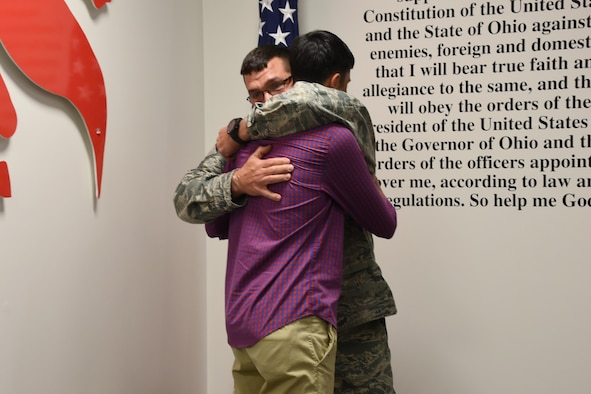 Senior Master Sgt. Roger Burton, the fire chief at the 179th AW, embraces his son Cooper Burton on Dec. 2, 2016, at the 179th Airlift Wing, Mansfield, Ohio. They both recited the oath of enlistment, Cooper for the first time and his father for the last time. Cooper is starting his first term as a crew chief for the 179th AW and Chief Burton is starting his final term of his career. (U.S. Air National Guard photo by Airman Megan Shepherd/Released)