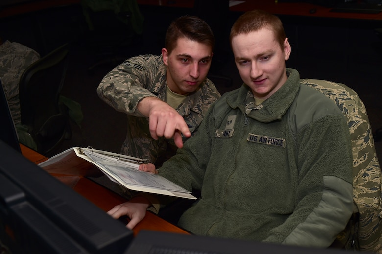 Senior Airman Jacob Bercel, 8th Space Warning Squadron satellite systems operator, helps fellow classmate, Senior Airman Samuel Hunt, 2nd Space Warning Squadron satellite systems operator, Jan. 19, 2017, during a class on Buckley Air Force Base, Colo. The class was for space operators to learn more about commanding satellites and responding to anomalous conditions on the satellites. The Buckley AFB helping agencies allow operators to focus on the 460th Space Wing mission. (U.S. Air Force photo by Airman 1st Class Gabrielle Spradling/Released)