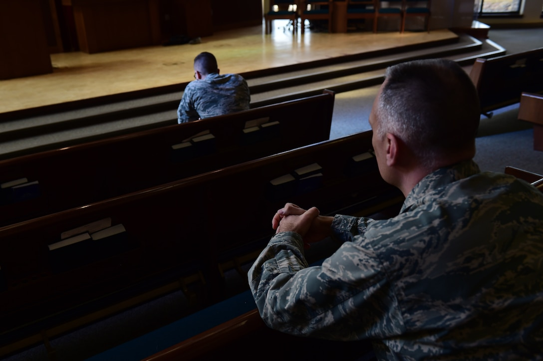 Chaplain (Maj.) Kevin Chelf, 460th Space Wing deputy wing chaplain, and Senior Airman Nicholas Pulkownik, 460th Operations Support Squadron staff instructor, take a moment of reflection Feb. 9, 2017, at the chapel on Buckley Air Force Base, Colo. The chapel is a spiritual outlet that focuses on the individual needs of each Airman. (U.S. Air Force photo by Airman 1st Class Gabrielle Spradling/Released)
