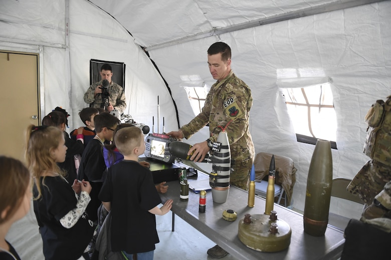Staff Sgt. Evan Dieckhoff, 49th Civil Engineer Squadron Explosive Ordnance Disposal technician, holds a plastic mock artillery projectile to a student during Operation Kids Investigating Deployment at Holloman Air Force Base, N.M., Feb. 3, 2017. Operation KID is an annual event allowing children of military members to acquire a better understanding of what their parents go through prior to a deployment. Military children were given a walk around the Basic Expeditionary Airfield Resources compound to see a mock deployment site, have a mission brief, paint their faces, try on Mission Oriented Protective Posture gear, and learn about different equipment including the opportunity to see a robot demonstration from Holloman's EOD unit. (U.S. Air Force photo by Staff Sgt. Stacy Jonsgaard)