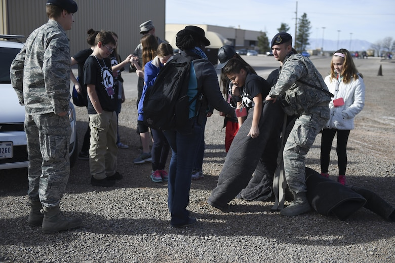 A group of children take turns wearing the bite suit with help from the 49th Security Forces Squadron Military Working Dog team with during Operation Kids Investigating Deployment at Holloman Air Force Base, N.M., Feb. 3, 2017. Operation KID is an annual event allowing children of military members to acquire a better understanding of what their parent goes through prior to a deployment. Military children were given a walk around the Basic Expeditionary Airfield Resources compound to see a mock deployment site, a mission brief, painted their faces, tried on Mission Oriented Protective Posture gear, and learn about different equipment including the opportunity to see a robot demonstration from Holloman's EOD unit. (U.S. Air Force photo by Staff Sgt. Stacy Jonsgaard)