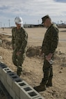 Ensign Frank Sysko, detachment Twentynine Palms Officer in Charge, Naval Mobile Construction Battalion 3, and Brig. Gen. William F. Mullen III, Combat Center Commanding General, tour the construction of the diversion walls in progress at Camp Wilson aboard Marine Corps Air Ground Combat Center, Twentynine Palms, Calif., Feb. 2, 2017. NMCB 3 is in Camp Wilson for three weeks working on the construction of displacement walls and K-Span units for their upcoming deployment in April. (U.S. Marine Corps photo by Lance Cpl. Dave Flores)
