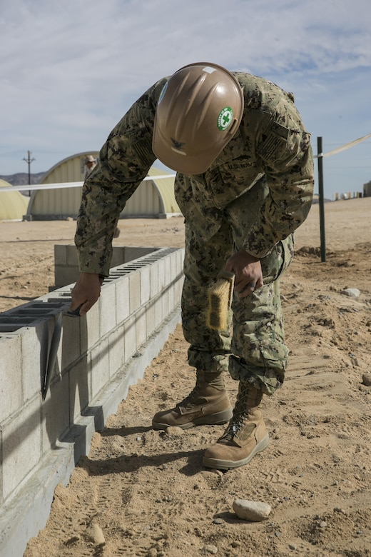 Petty Officer 2nd Class, Bronson Bond, builder, Naval Mobile Construction Battalion 3, works on a displacement wall at Camp Wilson aboard Marine Corps Air Ground Combat Center, Twentynine Palms, Calif., Feb. 2, 2017. NMCB 3 is in Camp Wilson for three weeks working on the construction of displacement walls and K-Span units for their upcoming deployment in April. . (U.S. Marine Corps photo by Lance Cpl. Dave Flores)