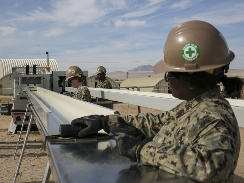 U.S. Navy Seabees with Naval Mobile Construction Battalion 3 prepare sheets of metal while constructing K-Span units at Camp Wilson aboard Marine Corps Air Ground Combat Center, Twentynine Palms, Calif., Feb. 2, 2017. NMCB 3 is in Camp Wilson for three weeks working on the construction of displacement walls and K-Span units for their upcoming deployment in April.  (U.S. Marine Corps photo by Lance Cpl. Dave Flores)