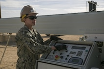 Petty Officer 3rd Class Laine Roman, main operator, Naval Mobile Construction Battalion 3, turns on the K-Span Machine to create the metal sheets used to create the K-Span units at Camp Wilson aboard the Marine Corps Air Ground Combat Center, Twentynine Palms, Calif., Feb. 2, 2017. NMCB 3 is in Camp Wilson for three weeks working on the construction of displacement walls and K-Span units for their upcoming deployment in April. (U.S. Marine Corps photo by Lance Cpl. Dave Flores)