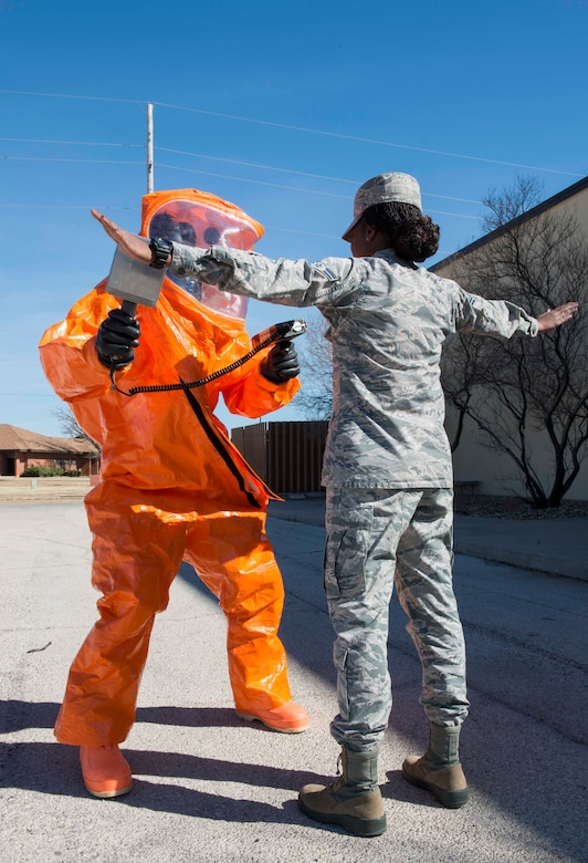 U.S. Air Force 1st Lt. Zachary Spranger, 7th Civil Engineer Squadron readiness and emergency management flight commander, (left) uses an ADM-300 tool to search for alpha radiation on Airman 1st Class Julia Scholar, 7th CES emergency management logistics, at Dyess Air Force Base, Texas, Feb. 8, 2017. The Dyess Air Force Base readiness and emergency management flight prepares, plans, trains, educates and equips installation personnel to respond to major accidents, natural disasters, weapons of mass destruction, and wartime chemical, biological, radiological and nuclear attacks. They provide technical expertise to commanders during response operations and perform detection, monitoring, warning and reporting in an effort to save lives, minimize the loss or degradation of resources and restore operational capability. (U.S. Air Force photo by Airman 1st Class Austin Mayfield)