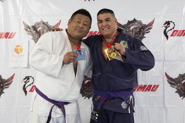 U.S. Marine Corps Master Sgt. Marcos Martinez, expeditionary fire rescue staff noncommissioned officer in charge with Marine Wing Support Squadron (MWSS) 171, right, poses for a photo with his opponent during the Duamau Tournament, a jiu jitsu competition at the TK Training Center in Hiroshima, Japan, Feb. 5, 2017. Jiu jitsu is a sport that teaches competitors to respect their opponents and build on the differences. Martinez trains among other Marines at the Iron Works North gym on Marine Corps Air Station Iwakuni. (U.S. Marine Corps photo by Lance Cpl. Joseph Abrego)