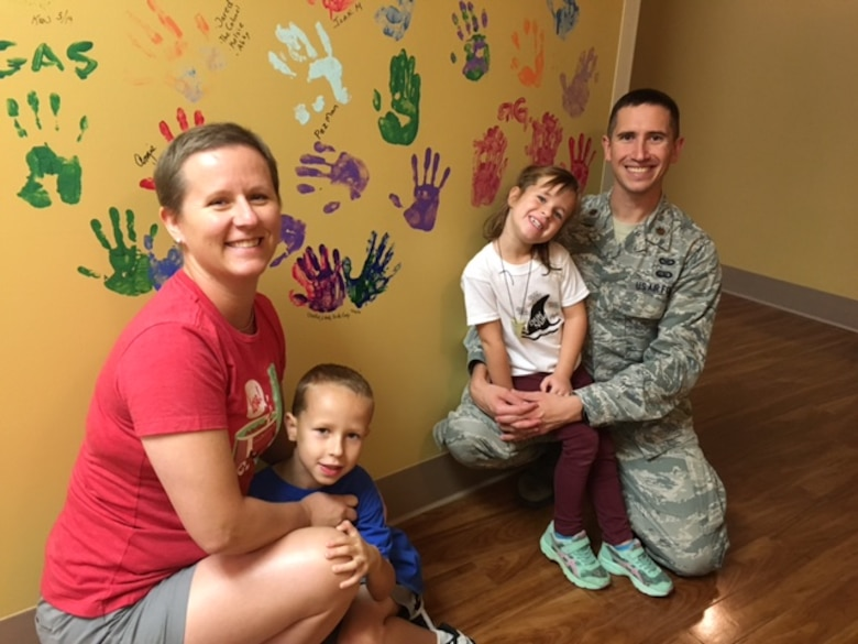 The Daniels family poses in front of the radiation treatment room's victory wall, Sept. 26, 2016, at the San Antonio Military Medical Center with the hand prints of everyone who has gone through treatment in that room. The Daniels family's hand prints are between them. (Courtesy photo)