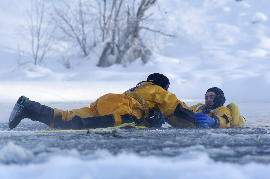 Airman 1st Class Joseph Humphrey (left), an Air Force fire protection specialist, and Airman 1st Class Tyler Parmelee conduct ice water rescue training at Joint Base Elmendorf-Richardson, Alaska, Feb. 4, 2017. The training taught the JB Elmendorf-Richardson firefighters self-rescue techniques, victim recovery and certified them as ice water rescue technicians. Humphrey and Parmelee, natives of Ridgecrest, Calif., and Ashburn, Va., are assigned to the 673rd Civil Engineer Squadron. (U.S. Air Force photo/Alejandro Pena)