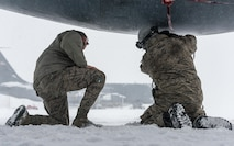 Maintenance personnel close an engine cowling on a KC-135R at the 101st Air Refueling Wing, Bangor, Maine, Feb. 5, 2015.  The northeast is having a record breaking season of blizzards and snow accumulation and Airmen of the Maine Air National Guard perform outdoor duties in some of the harshest weather of the year.  (Air National Guard Photo by Master Sgt. Jon Duplain/Release)