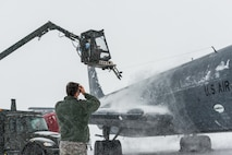 Staff Sgt. Andrew Sinclair, a broadcast journalist, films a KC-135R being deiced at 101st Air Refueling Wing, Bangor, Maine, Feb. 5, 2015.  The northeast is having a record breaking season of blizzards and snow accumulation and airmen of the Maine Air National Guard perform outdoor duties in some of the harshest weather of the year.  (Air National Guard Photo by Master Sgt. Jon Duplain/Release)