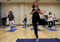 Taylor Plantin, a fitness instructer, instructs a yoga class at the Whiteman Air Force Base, Missouri, fitness center Feb. 7, 2017. The class takes place on Tuesdays at 5 p.m. and it is designed to to help participants synchronize their breathing with movement.