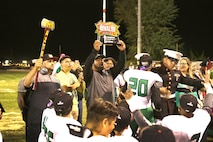 The coach for Victor Valley High School raises the Great American Rivalry Series Trophy Oct. 7. Victor Valley beat Barstow High School to claim the title.