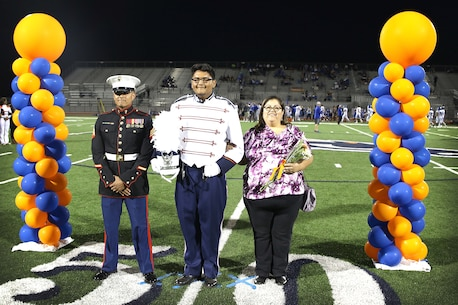 Sgt Frank Duran escorts Future Marine David Carter during senior night at Roosevelt High School Nov. 4. Carter was asked to bring someone that has influenced him in his life. Most students chose a teacher or a coach, he chose his recruiter.