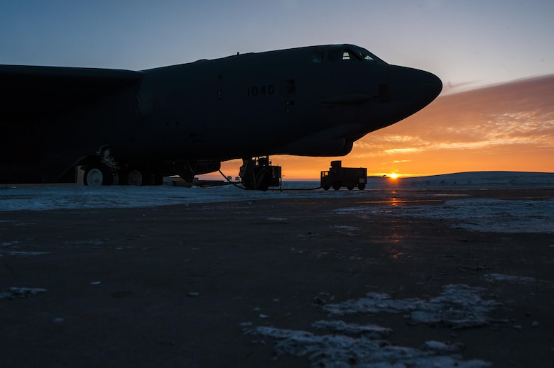 The sun rises behind a B-52H Stratofortress at Minot Air Force Base, N.D., Jan. 26, 2017. Airmen from the 5th Aircraft Maintenance Squadron work around the clock in all weather conditions to provide B-52 firepower on demand. (U.S. Air Force photo/Senior Airman J.T. Armstrong)