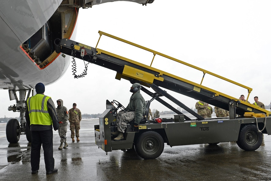 Staff Sgt. Christopher Craig (center), 62nd Aerial Port Squadron ramp services technician, pulls a ramp up to a transient aircraft Feb. 8, 2017 at Joint Base Lewis-McChord, Wash. Within the APS, the air terminal operations center manages the PAX terminal, ramps services section (loading and unloading of cargo), fleet services (cleaning the aircraft) and the special handling section (handling explosives). (U.S. Air Force photo/Senior Airman Divine Cox)