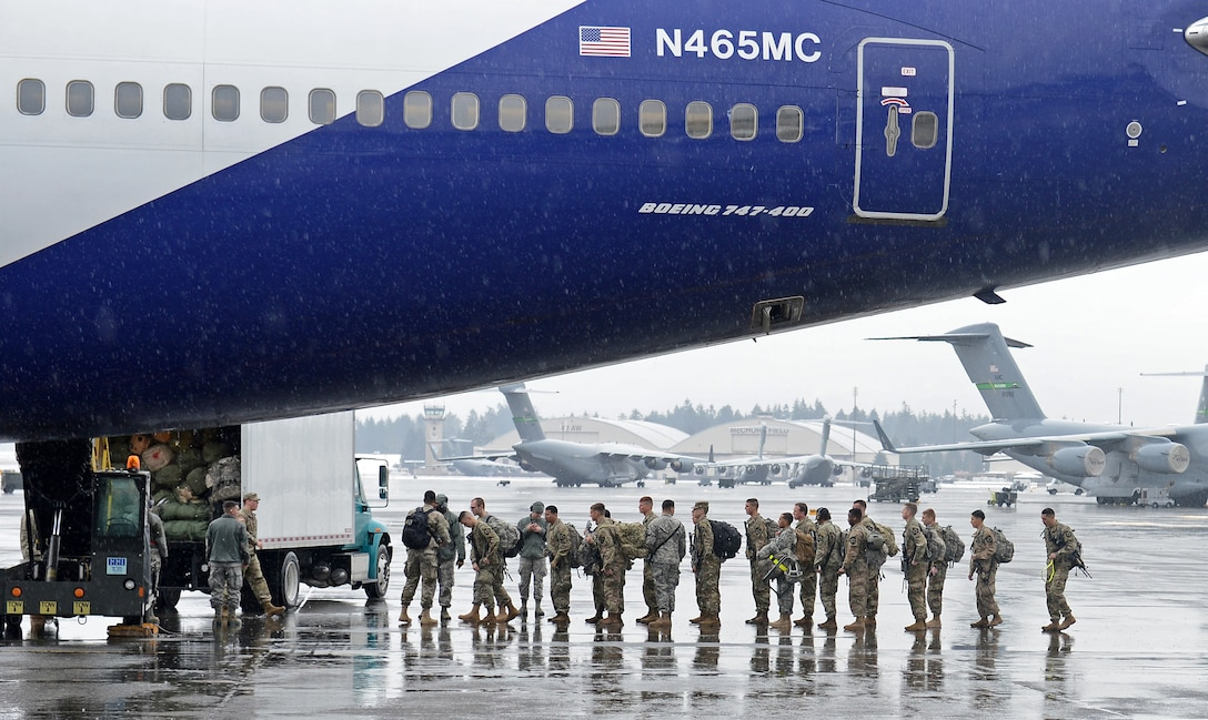 Airmen from the 62nd Aerial Port Squadron passenger service, escort Army soldiers from the 3rd Stryker Brigade to their aircraft Feb. 8, 2017 at Joint Base Lewis-McChord, Wash. The PAX terminal is one of four sections that the air terminal operations center coordinates through to get passengers and their cargo to the aircraft. (U.S. Air Force photo/Senior Airman Divine Cox)
