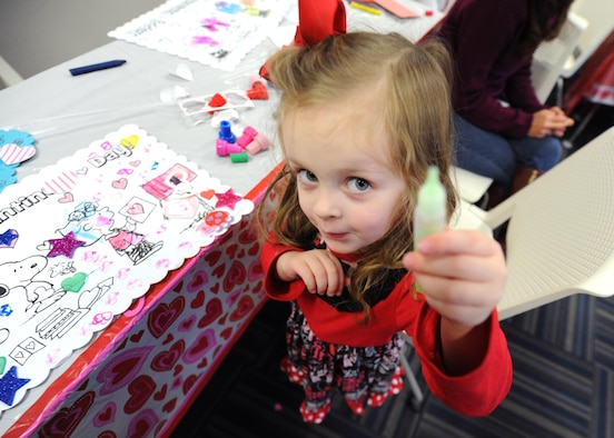Harper Boccher, a 4-year-old, chooses a color of glitter glue for her card Feb. 4, 2017, during the Exceptional Family Member Program's Valentine's Day event, at the Airman & Family Readiness Center on Little Rock Air Force Base, Ark. A variety of craft supplies provided by the EFMP was available for the children to select from. (U.S. Air Force photo by Airman 1st Class Grace Nichols)