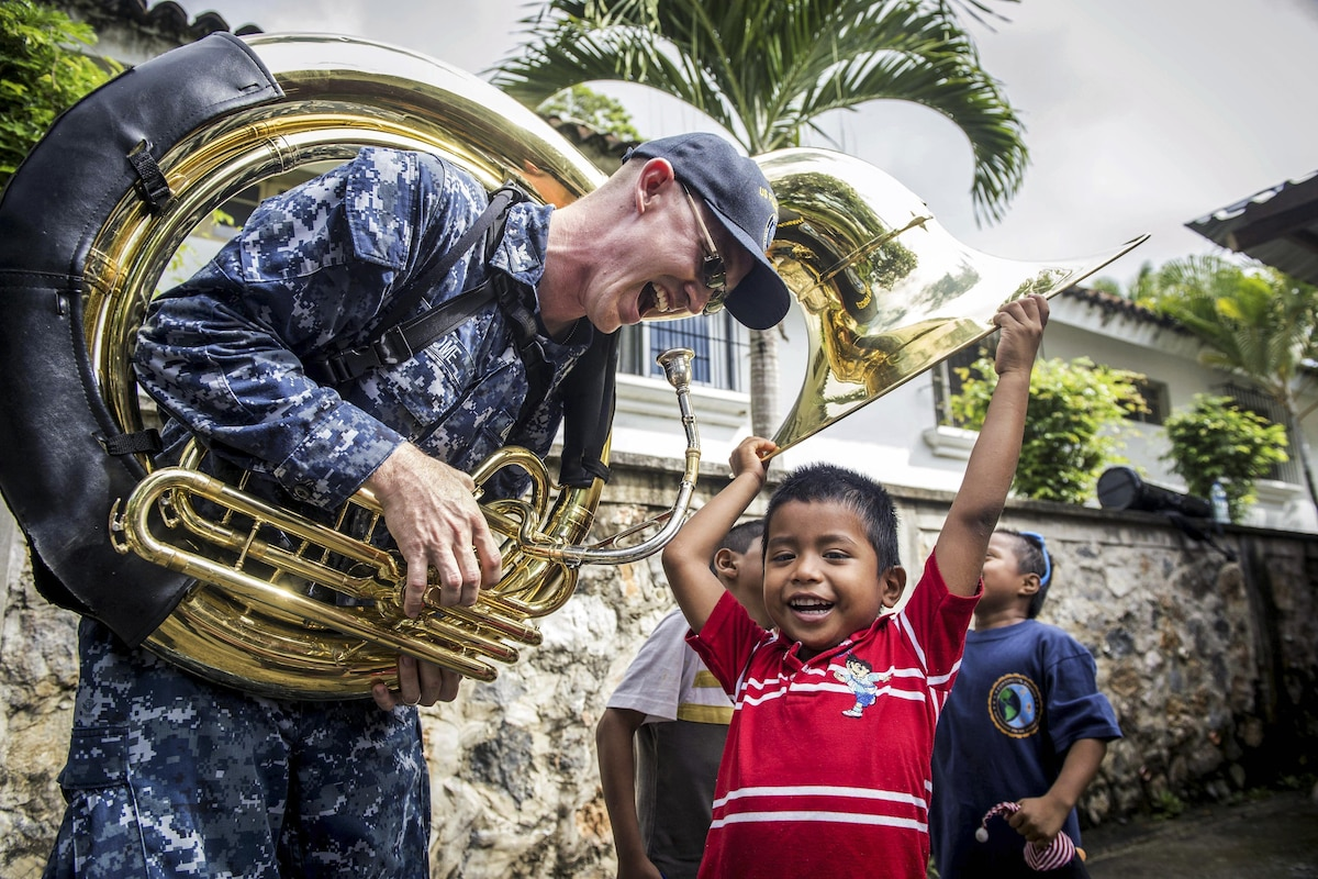 A sailor plays a musical instrument with a child.