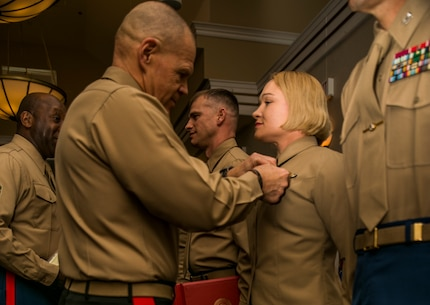 Gen. Robert B. Neller, Commandant of the Marine Corps, awards Staff Sgt. Christin J. McAdams with 6th Communications Battalion, Force Headquarters Group, with the Navy and Marine Corps Commendation Medal for her outstanding efforts as an active reserve career planner during the annual Commandant of the Marine Corps' 2016 Combined Awards Ceremony, Feb. 8, 2017, in Quantico, Va.  Reserve career planners work hard to retain, train and prepare both active duty and reserve Marines for what is next in their future or career that best fits their unique individual needs.
