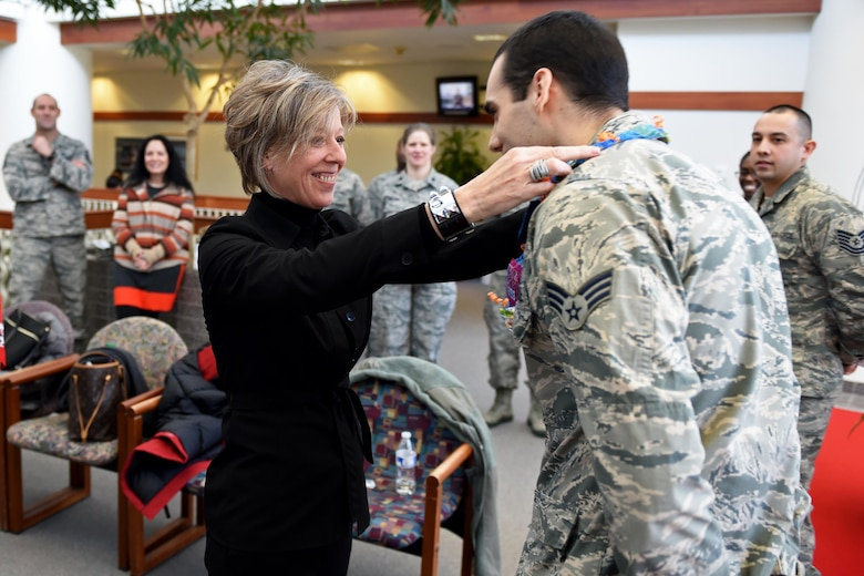 Donna O'Shaughnessy, spouse of Gen. Terrence O'Shaughnessy, commander of Pacific Air Forces, presents a candy-lei to Senior Airman Benjamin Haase, an Airman with the 673d Medical Operation Squadron, at the Joint Base Elmendorf- Richardson (JBER) hospital, Feb. 7, 2017. Mrs. O'Shaughnessy also had the chance to visit with JBER first sergeants' spouses to discuss current issues and concerns on the installation.
