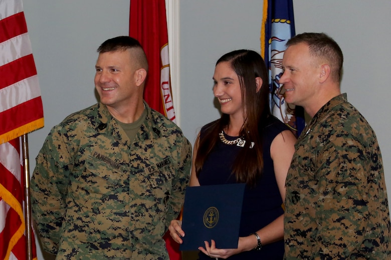 Stacy Mergen, center, was awarded for her efforts as a volunteer for the Navy-Marine Corps Relief Society during an annual banquet aboard Marine Corps Air Station Cherry Point, N.C., Feb. 9, 2017. Sgt. Maj. Benjamin Pangborn, left, and Col. Todd Ferry distributed awards based on hours and efforts donated to the society. Ferry is the commanding officer of MCAS Cherry Point and Pangborn is the air station sergeant major. (U.S. Marine Corps photo by Cpl. Jason Jimenez/ Released)