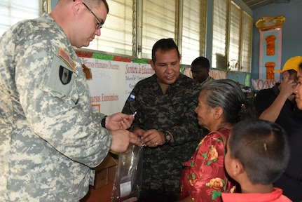 Sgt. Maj. Wilson Carranza from the Honduran Armed Forces Surgeon's Office and U.S. Army Sgt. 1st Class Bradley Niekamp, Joint Task Force-Bravo Medical Element Preventive Medicine, provide vitamins and deworming medication to a family in Estancia, La Paz during a Medical Readiness Training Exercise Jan. 31. A preventive medicine class was also given where people learned about the importance of sanitary precautions for the prevention of diseases, as well as personal hygiene. (U.S. Army photo by Maria Pinel)