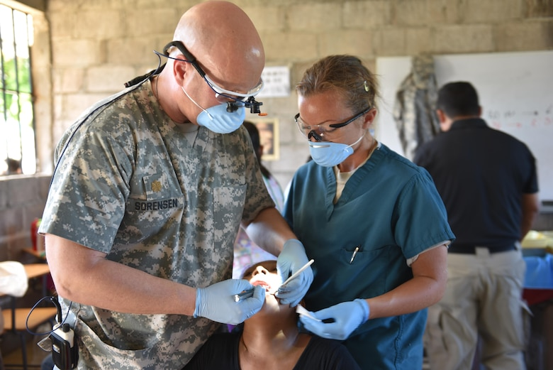 U.S. Army Maj. Eric Sorensen and Sgt. Charissa Youngs, Joint Task Force-Bravo Medical Element, perform an extraction on a patient during a Medical Readiness Training Exercise in Estancia, La Paz, Jan. 31. Personnel from JTF-Bravo worked side by side with local nurses and physicians, as well as Honduran soldiers to provide the population with immunizations, preventive medicine, dental services, basic medical care and pharmacy services during the two-day mission. (U.S. Army photo by Maria Pinel)