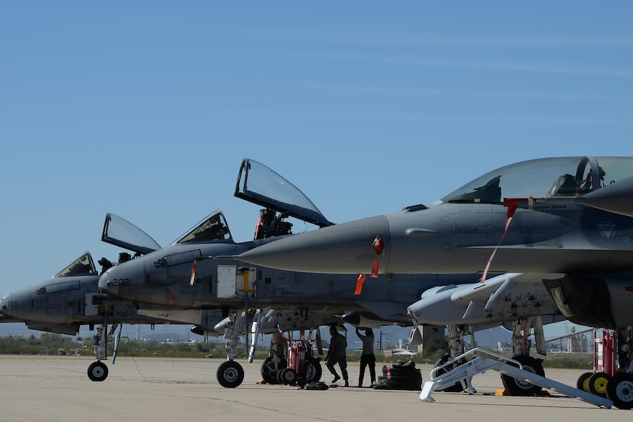 Two U.S. Air Force A-10C Thunderbolt IIs and an F-16 Fighting Falcon rest on the flightline during the 2017 Heritage Flight Training and Certification Course at Davis-Monthan Air Force Base, Ariz., Feb. 10, 2017. The modern aircraft that participated in this year's HFTCC were the F-35 Lightning II, the F-22 Raptor, F-16 Fighting Falcon and the A-10C Thunderbolt II. The historic aircraft included the P-51 and T-51 Mustangs, the P-40 Warhawk, the P-38 Lightning, the P-47 Thunderbolt, the T-33 Shooting Star and the F-86 Sabre. (U.S. Air Force photo by Senior Airman Ashley N. Steffen)