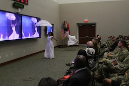 U.S. Army Central Soldiers watch members of the Kerende Dance Group perform while a clip of the Alvin Dance Company plays in the background during the USARCENT African American History observance, Feb. 8, at Shaw Air Force Base, S.C.