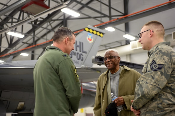 Retired Lt. Col. James H. Harvey III (center), member of the historic Tuskegee Airmen, talks to Col. David Smith, 419th Fighter Wing commander, and Tech. Sgt. David Batman, 419th Aircraft Maintenance Squadron, about the F-16 Fighting Falcon during a tour at Hill Air Force Base Feb. 11. (U.S. Air Force photo/Bryan Magaña)