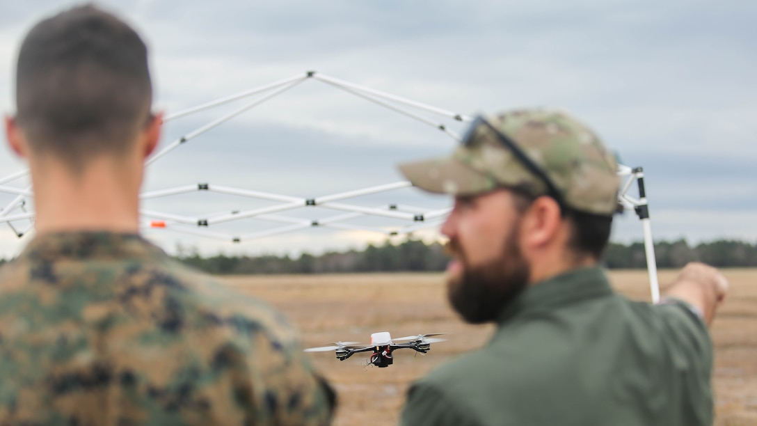 Shaun Sorensen, right, a small unmanned aerial systems instructor with Training and Logistics Support Activity, instructs a Marine with Task Force Southwest, left, on flying maneuvers of the Instant Eye SUAS at Marine Corps Base Camp Lejeune, North Carolina, Feb. 8, 2017. The Instant Eye is revolutionary in that it can fly easily into buildings, over walls and hills, and can take off and land vertically. Approximately 300 Marines are assigned to Task Force Southwest, whose mission will be to train, advise and assist the Afghan National Army 215th Corps and 505th Zone National Police.