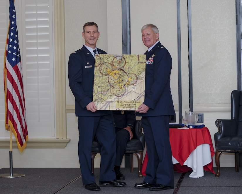 (From left) 317th Airlift Squadron Commander, Lt. Col. Stan Davis, presents retiring, Lt.. Col. Rick Davis, 317th AS, with a gift of a Charleston air space map during his retirement ceremony at Joint Base Charleston, S.C Feb. 12. (U.S. Air Force photo by Senior Airman Tom Brading)