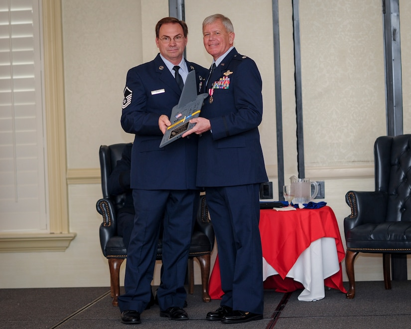 (From left) Master Sgt. Eugene Rorie, 317th Airlift Squadron loadmaster, , presents retiring, Lt.. Col. Rick Davis, 317th AS, with a gift of a Charleston T-tail during his retirement ceremony at Joint Base Charleston, S.C Feb. 12. (U.S. Air Force photo by Senior Airman Tom Brading)