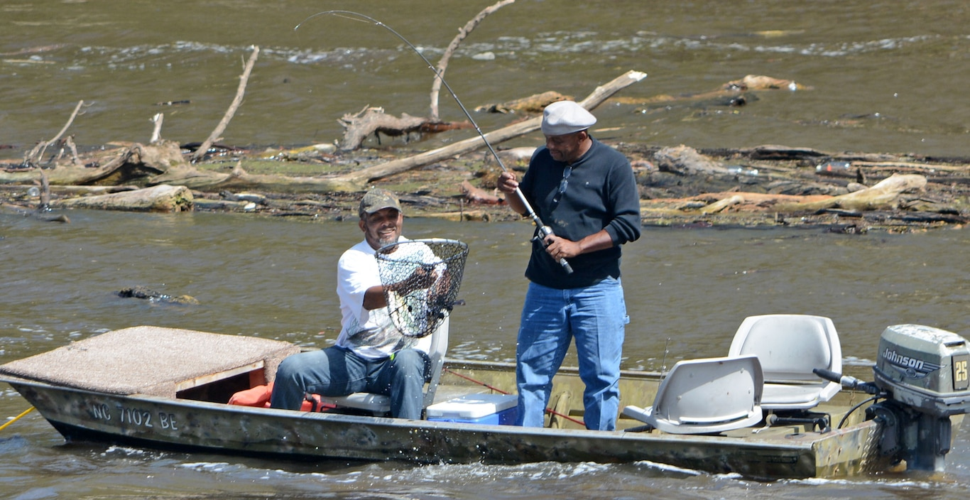 Two fisherman land an American shad fish at Lock and Dam 1.