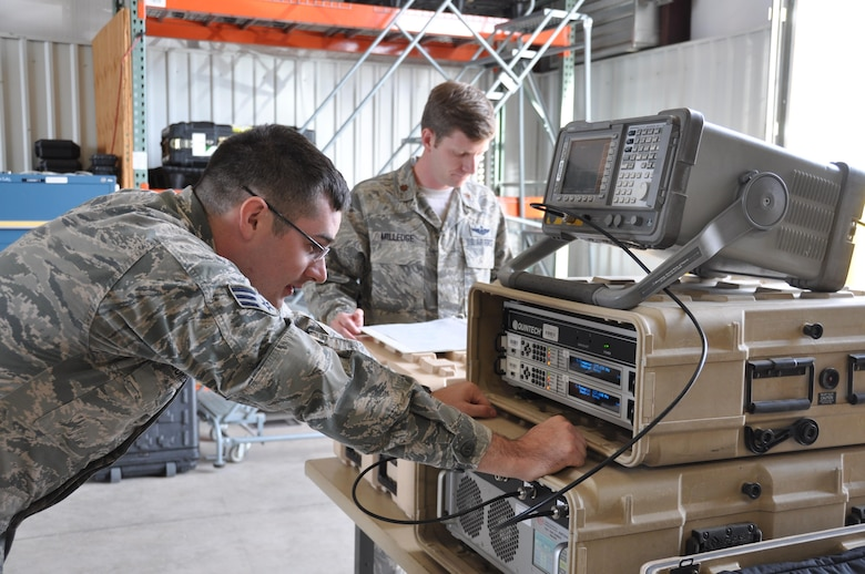 (Front to rear) Senior Airman Richard Sorensen and Maj. Aaron Milledge, GPS denial operators, set up high-power GPS electromagnetic interference training equipment. The hardware suite consists of a spectrum analyzer that verifies that the antenna and power are operating within safe parameters, a modem that builds a signal, and a high-powered amplifier. (U.S. Air Force photo/Maj. Jessica D'Ambrosio)