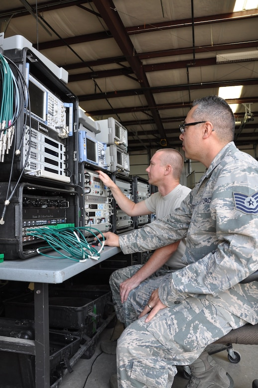 (Front to rear) Tech. Sgt. Matthew Guterriz, threat analyst, and Tech. Sgt. Kevin Broyles, radio frequency transmissions technician, set up satellite communication equipment for a training exercise. SATCOM is used to jam communications, replicating a contested environment for operators. SATCOM can be conducted from Schriever AFB for exercises happening at Nellis AFB. (U.S. Air Force photo/Maj. Jessica D'Ambrosio)