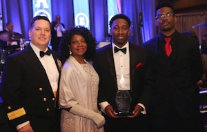 """WASHINGTON (Feb. 11, 2017) - Dwayne Nelson, Naval Surface Warfare Center (NSWC) Dahlgren Division engineer, holds his Black Engineer of the Year (BEYA) Community Service Award at the 31st annual BEYA gala. Standing left to right are NSWC Commander RDML Tom Druggan; Dwayne's mother, Linda; Dwayne; and his brother, Rudy. """"I would like to thank Rear Adm. Tom Druggan, the Rappahannock Big Brothers Big Sisters and the Naval Surface Warfare Center Dahlgren Division for supporting me throughout my career,"""" said Nelson. """"The endless encouragement and invaluable learning have changed me forever."""" (U.S. Navy photo/Released)"""