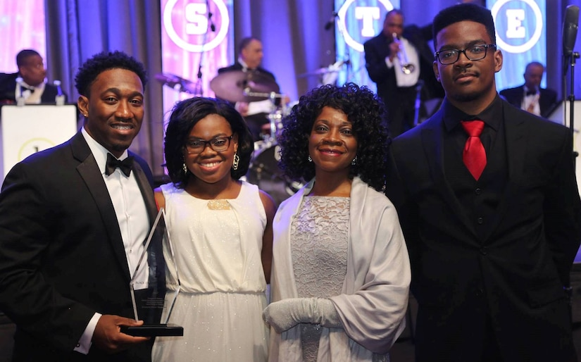 "WASHINGTON (Feb. 11, 2017) - Dwayne Nelson, Naval Surface Warfare Center Dahlgren Division engineer, holds his Black Engineer of the Year (BEYA) Award after being honored for his community service accomplishments at the 31st annual BEYA gala. Standing left to right are Dwayne; his sister, Olivia; mother, Linda; and brother, Rudy. ""To my family, friends, Alpha Phi Alpha fraternity brothers, and co-workers, a simple thank you is definitely not enough to tell you how much I wholeheartedly appreciate everything you've done for me,"" said Nelson. ""I never would have made it here without you. Your support has been amazing!"" (U.S. Navy photo by Rear. Adm. Tom Druggan/Released)"