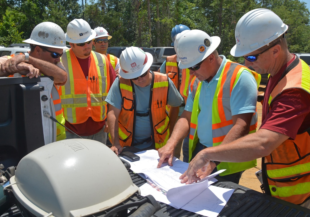 Regulatory Project Manager Brad Shaver, center, discusses the progress of construction of a highway in Brunswick County with local and state officials.