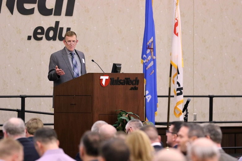 Gene Snyman, Tulsa District Small Business Office deputy, speaks at the 7th Annual Meet the Corps Day at Tulsa Technical Center in Owasso, Oklahoma.  Meet the Corps Day brought businesses and Tulsa District personnel together to talk about future contracts and exchange information.