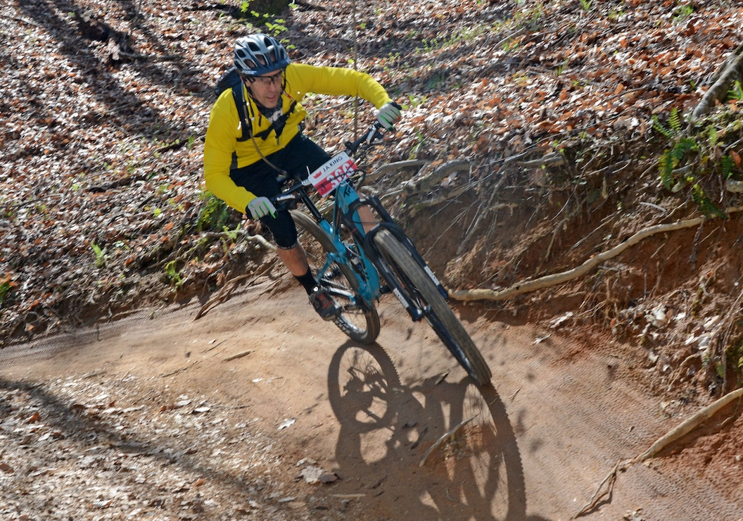 A mountain bicyclist rounds a high berm during the Six Hours of Warrior Creek mountain bike race at W. Kerr Scott Dam and Reservoir.