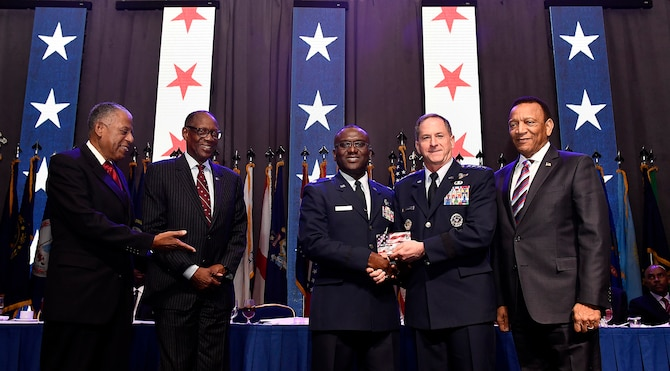 Air Force Chief of Staff Gen. David L. Goldfein, second from right, presents the Air Force Black Engineer of the Year Award to Lt. Col. Eric Amissah during the Black Engineer of the Year Awards Science, Technology, Engineering and Mathematics Conferences' Stars and Stripes ceremony Feb. 10, 2017, in Washington, D.C. (U.S. Air Force photo/Scott M. Ash)