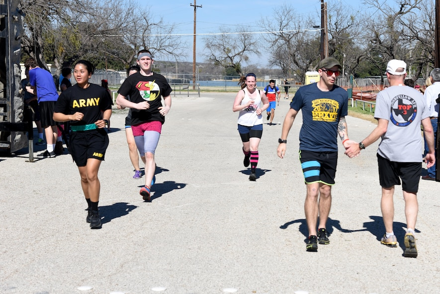U.S. Air Force Col. Michael Downs, 17th Training Wing Commander, congratulates runners as they finish the Polar Bear Party 5K at the Goodfellow Air Force Base Recreation Camp in San Angelo, Texas, Feb. 11, 2017. After the run, participants also got the chance to take a plunge into Lake Nasworthy. (U.S. Air Force photo by Staff Sgt. Joshua Edwards/Released)