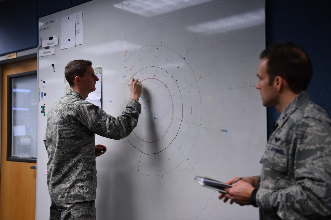 1st Lt. Krosby Keller (left), 225th Air Defense Squadron senior director, and Capt. John Dalrymple, 225th ADS mission planning cell chief, practice possible air defense intercept scenarios for Super Bowl LI.  The FAA placed a temporary 30-mile radius flight restricted area around NGR Stadium during the Super Bowl during which WADS was responisble for guarding the skies as part of NORAD's Operation Noble Eagle air defense mission. (U.S. Air Force photo by Kimberly D. Burke)
