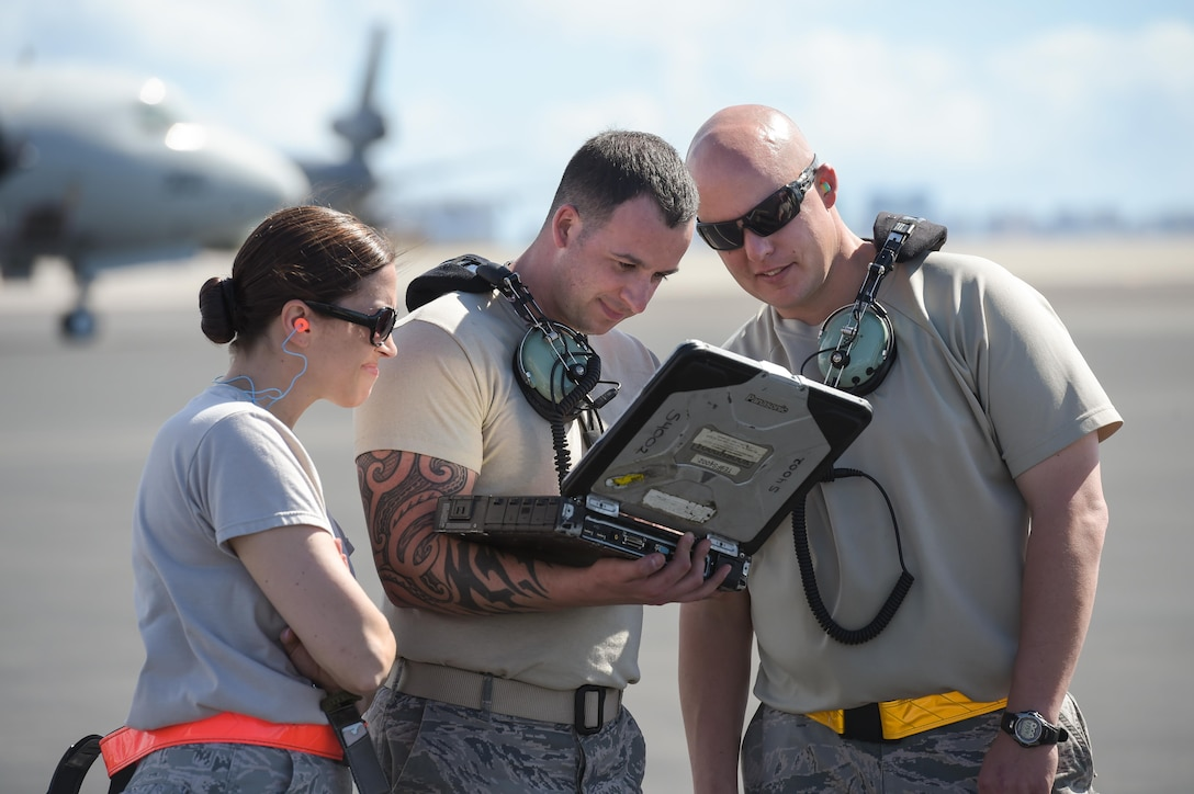 Master Sgt. Angela Leddy, Tech. Sgt. Andrew Mistowski and Master Sgt. Darrell Freel, Reservists assigned to the 513th Air Control Group, review a technical order on the flight line on Jan. 25 at Joint Base Pearl Harbor-Hickam, Hawaii. Reservists from the 513th Air Control Group deployed to the Hawaiian Islands to provide command and control for Sentry Aloha 17-01, a primarily Reserve and Air National Guard exercise that involves more than 40 aircraft and 1,000 personnel. (U.S. Air Force photo by 2nd Lt. Caleb Wanzer)