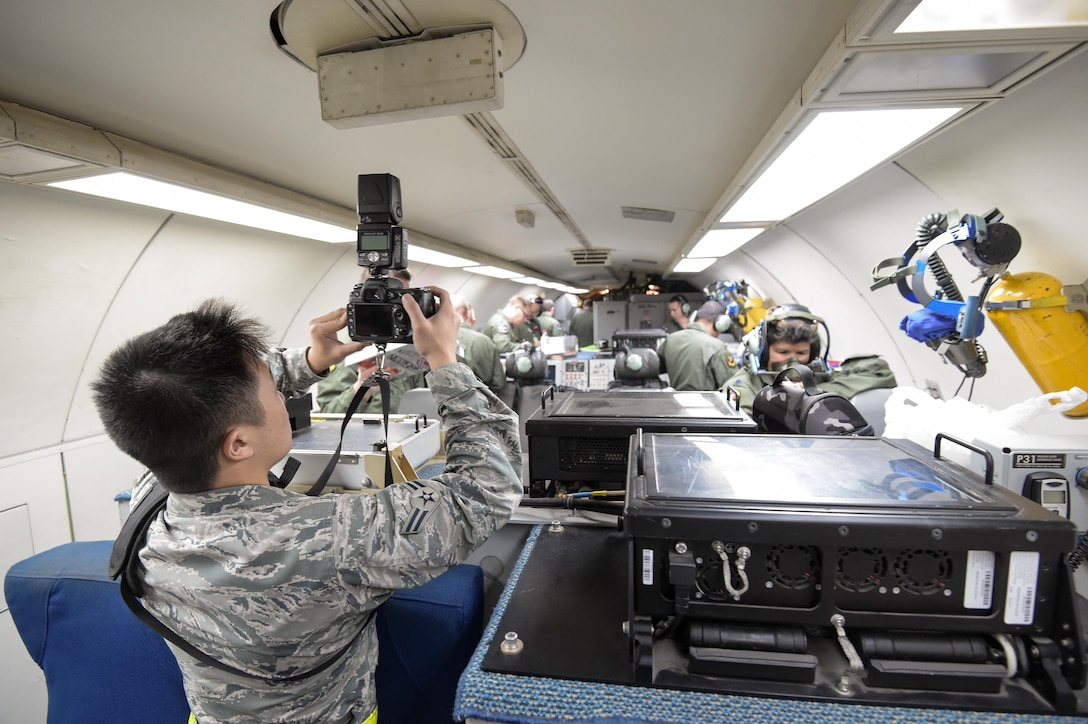 Airman 1st Class Stan Pak, a photojournalist assigned to the Hawaiian Air National Guard's 154th Wing, takes a photo on board an E-3 Sentry Jan. 31 before a mission in support of Sentry Aloha at Joint Base Pearl Harbor-Hickam, Hawaii. Reservists from the 513th Air Control Group deployed to the Hawaiian Islands to provide command and control for Sentry Aloha 17-01, a primarily Reserve and Air National Guard exercise that involves more than 40 aircraft and 1,000 personnel. (U.S. Air Force photo by 2nd Lt. Caleb Wanzer)